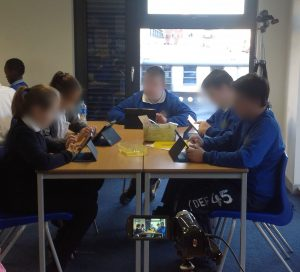 Children sitting at a desk using their iPads